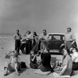 George Rodger, Total Eclipse of the Sun. Kuwaiti Oil Company personel and their families bring a picnic lunch to the desert to watch the eclipse. 1952.